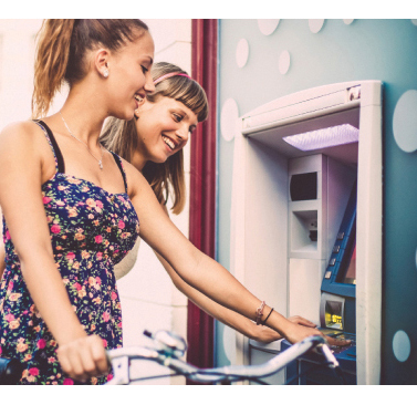 Photo of two teenage girls using an ATM one girl is riding a bicycle